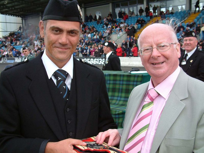 Gordon Brown Director of TG Drumming & Leading Drummer of Boghall & Bathgate Caledonia PB Grade 1, being presented with the winning Drumming Sash in June 2007 at the British Championships.
