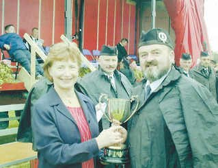 Sam Hodgen Pipe Major of 'Moneygore Pipe Band' being presented with the Cup for 2nd Place in Grade 3B, at Ahoghill Pipe Band Competition held on the 3rd of June 2000.